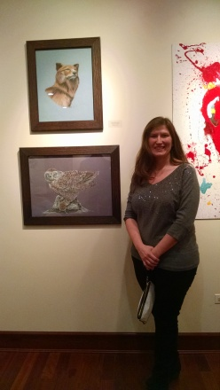 Northern grey wolf in pastel (top), Snowy owl in colored pencil (bottom).  Me standing with two of my pieces in the show.
